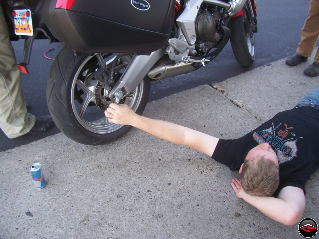 Man adjusting motorcycle chain on a Kawasaki Versys