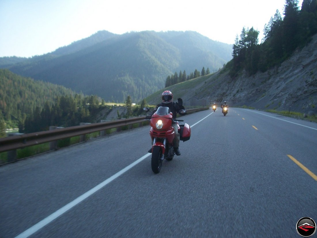 Motorcyle riding waving while riding Snake River Canyon near Alpine, Wyoming