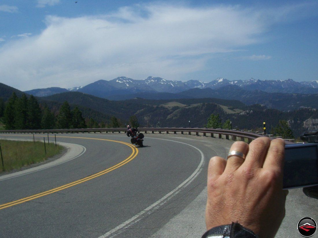 man taking a photo of a motorcycle riding through a swtichback corner