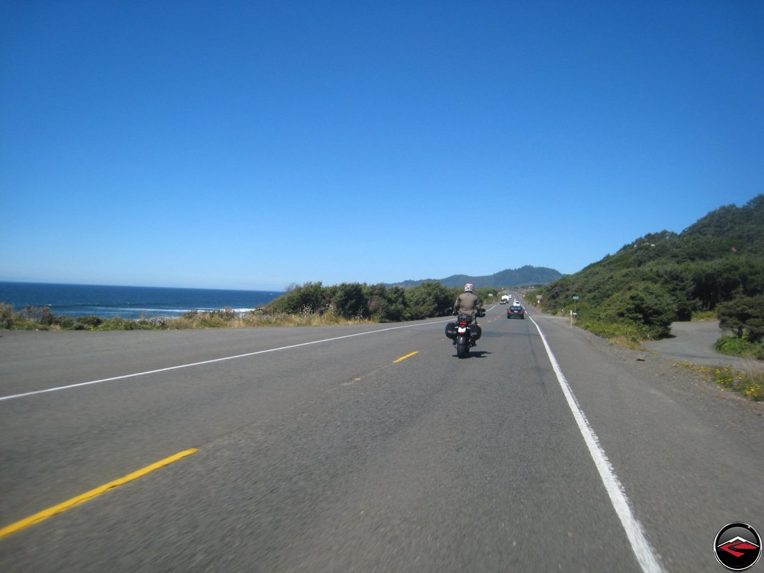 motoryclists standing on the footpegs while riding on the pacfic coast highway