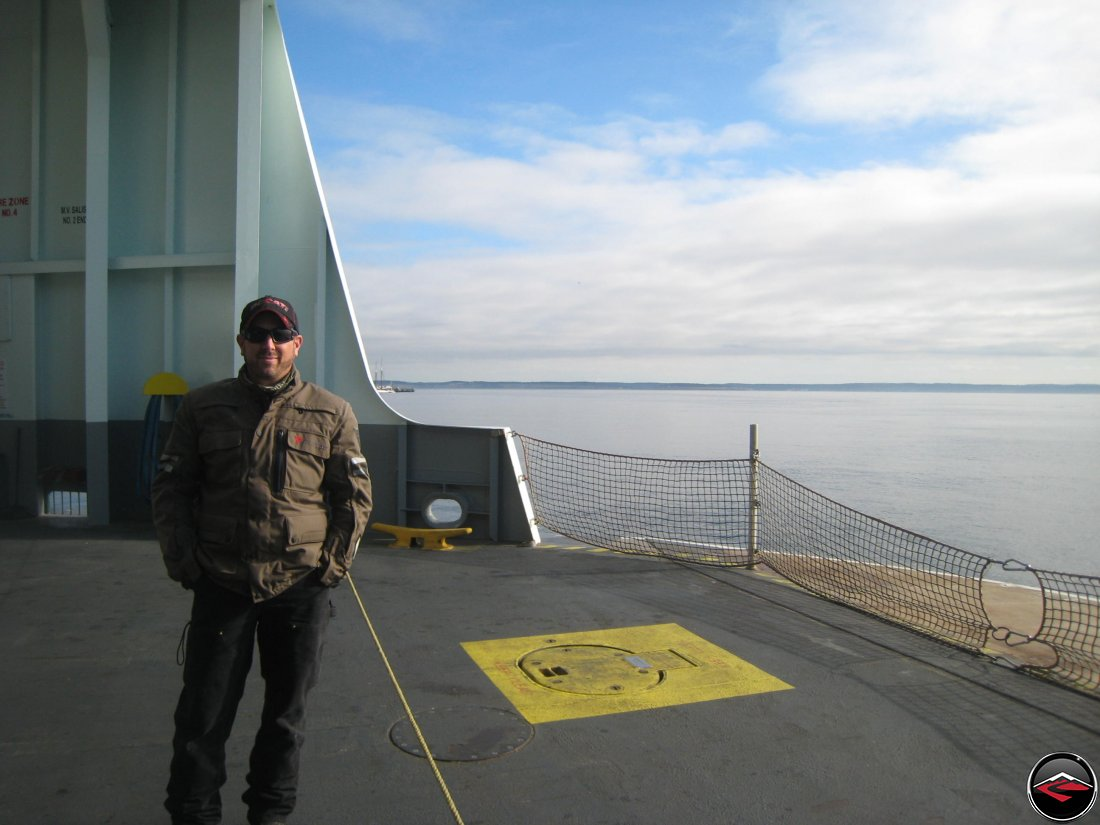man standing on the bow of a ferry boat