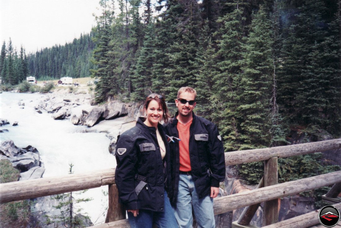 dave and kris standing on a wooden bridge in british columbia canada