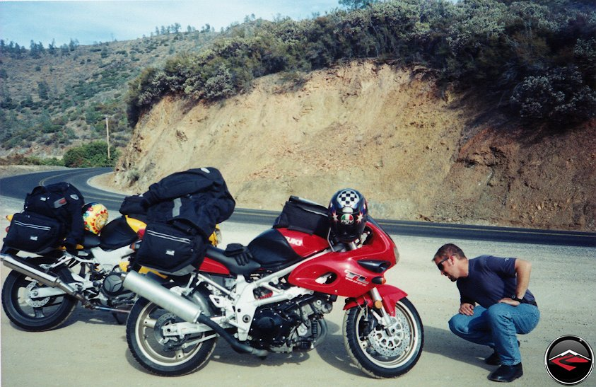 man checking tires on a Honda VTR1000 Superhawk and Suzuki TL1000S in a pullout