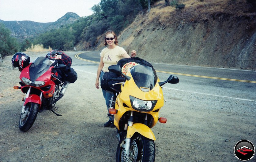 Pretty girl standing next to Honda Superhawk VTR1000 and Suzuki TL1000S