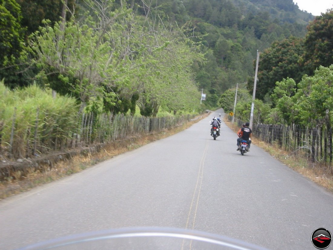 Motorcycles riding down a straight road in the Dominican Republic