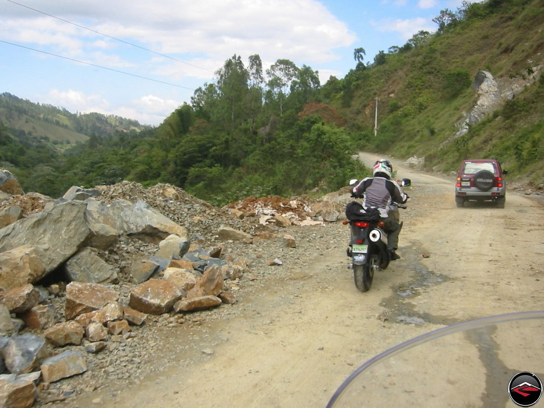 motorcycle navigating a gravel washout on a mountain road