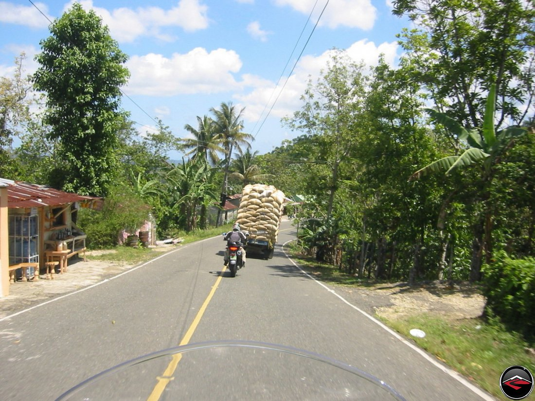 Motorcycle behind a truck with a dangerous load of bags