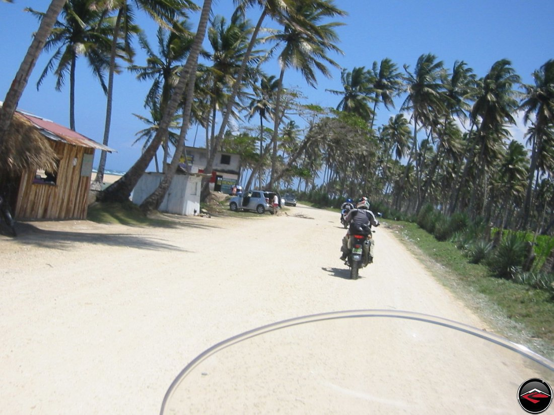 riding along the coast with palm trees and beach shacks
