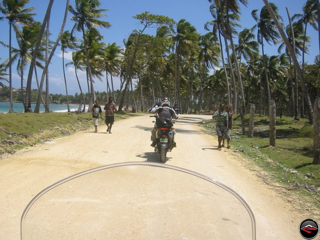 motorcycle riding down a Beautiful Caribbean coastal road with palm tree's and the atlantic ocean