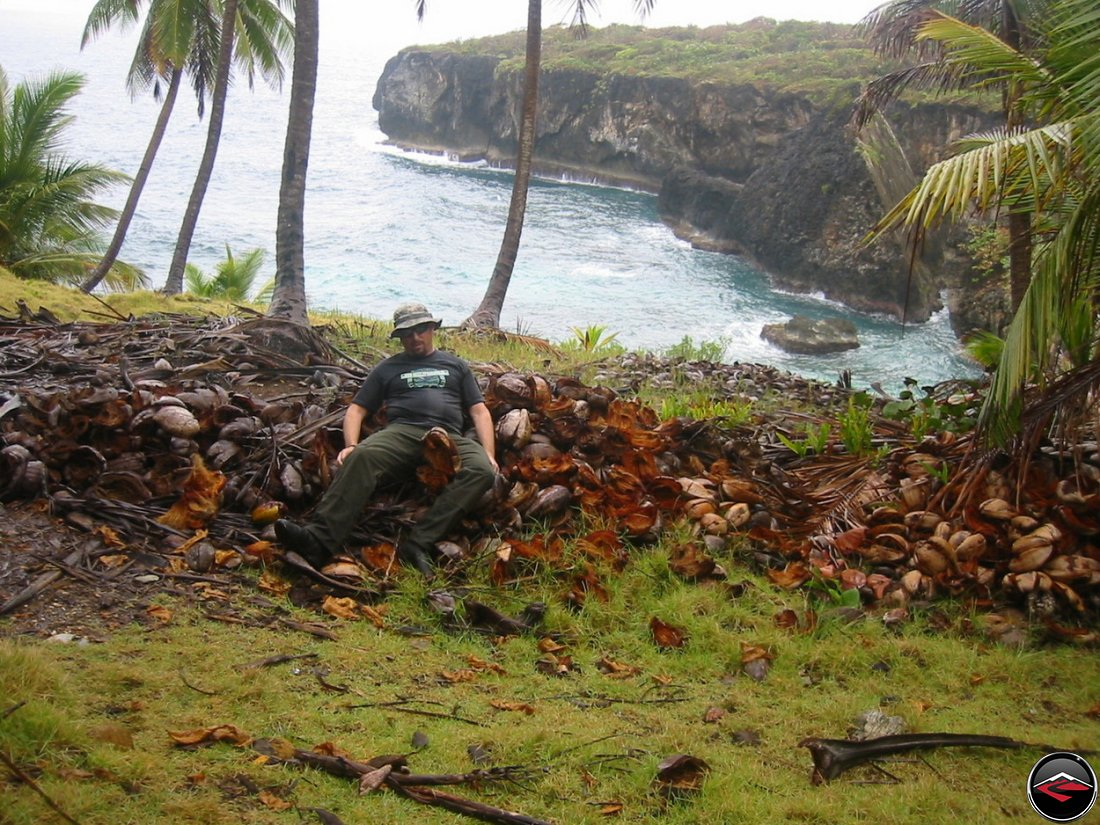 Man pretending to have eaten a giant pile of coconuts