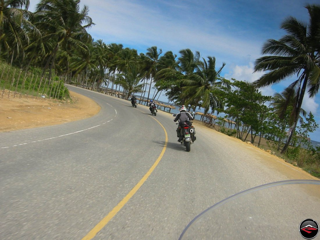motorcycles riding through an epic corner along the beach in the dominican republic