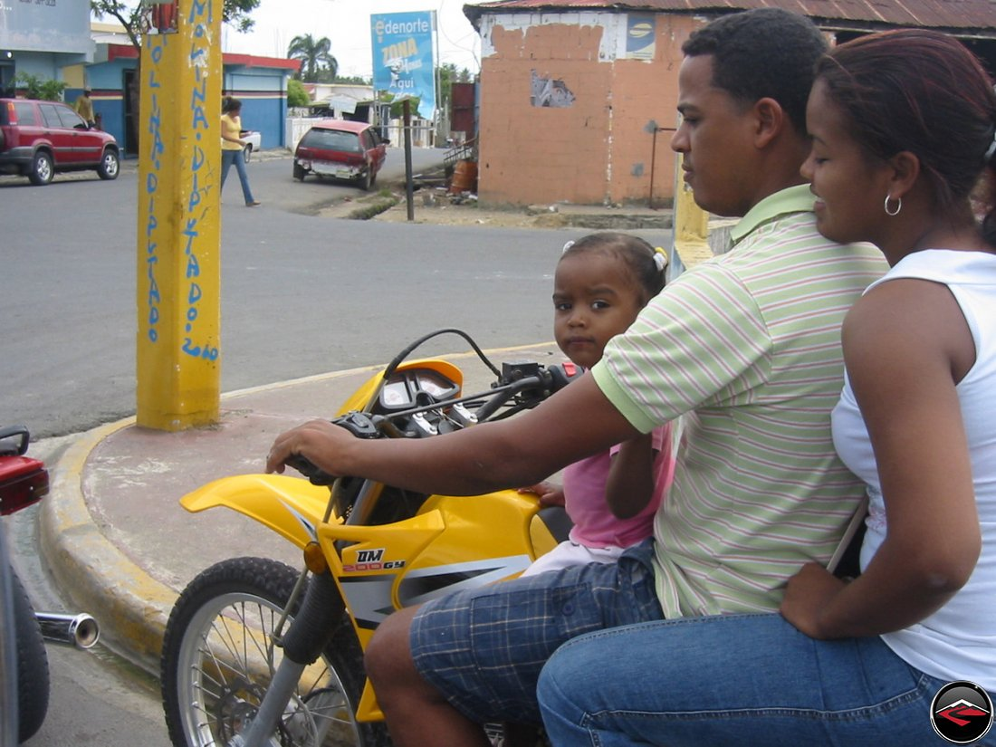 Three people on a small motorcycle in the dominican republic
