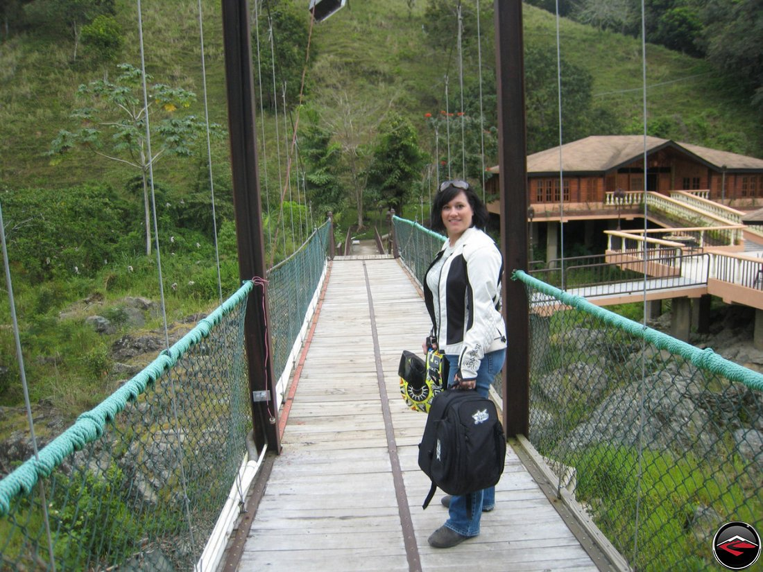 woman Crossing a wood and steel suspension bridge