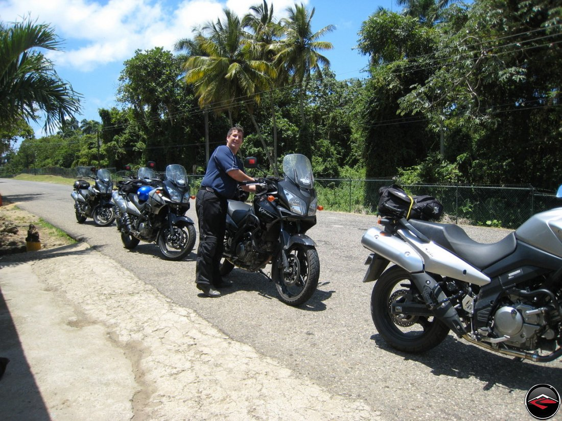 Suzuki V-Strom 650 motorcycles parked along the side of the road on a caribbean island