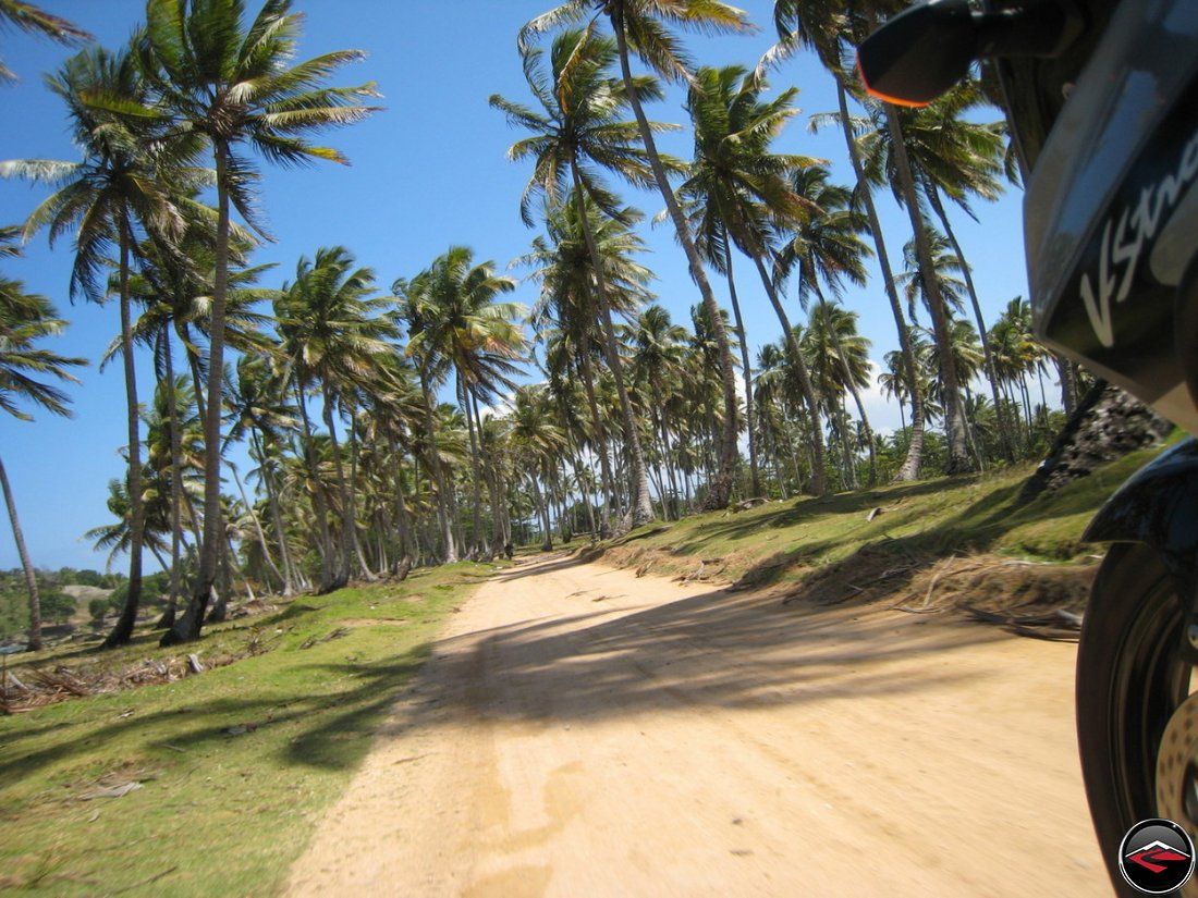 Motorcycle riding down a perfect sand road on a beach in the caribbean