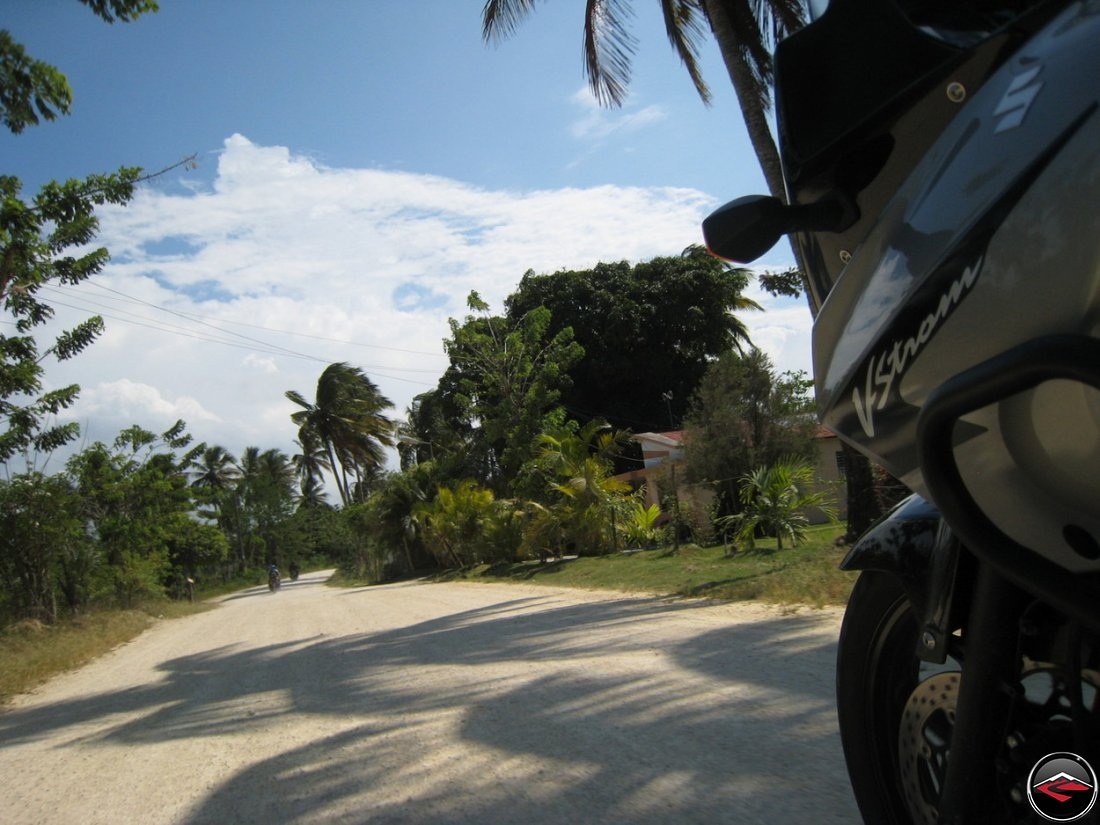 motorcycle riding down caribbean road with clouds over palm trees