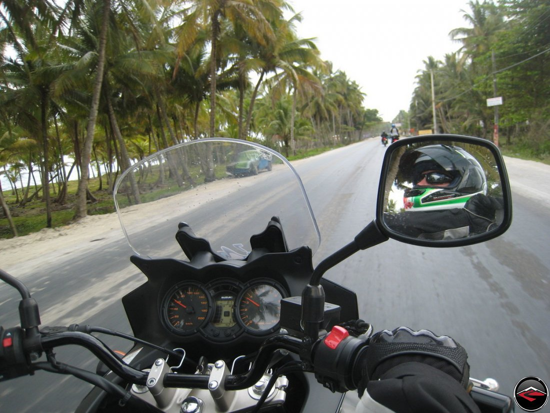 motorcycle rides down caribbean road while wind blows dust and palm trees