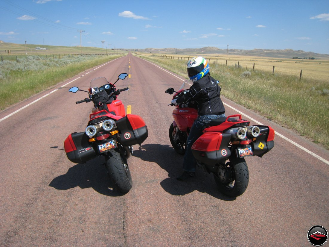 Two Ducati Multistrada's stopped in the middle of a red asphalt road near Recluse, Wyoming