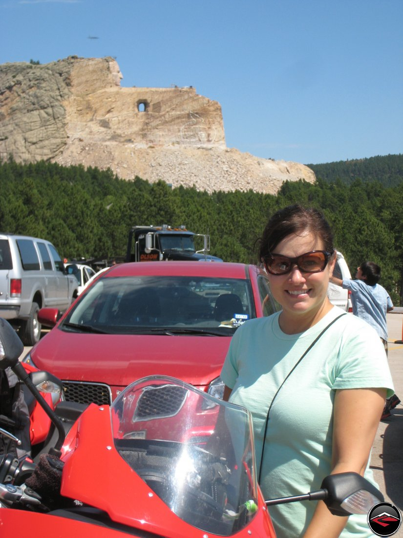 pretty girl standing in front of the unfinished Crazy Horse Monument in South Dakota