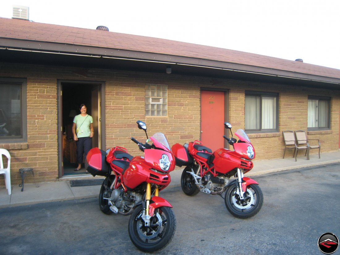 pretty girl standing behind two Ducati Multistrada motorcycles at the hotel in Sundance Wyoming