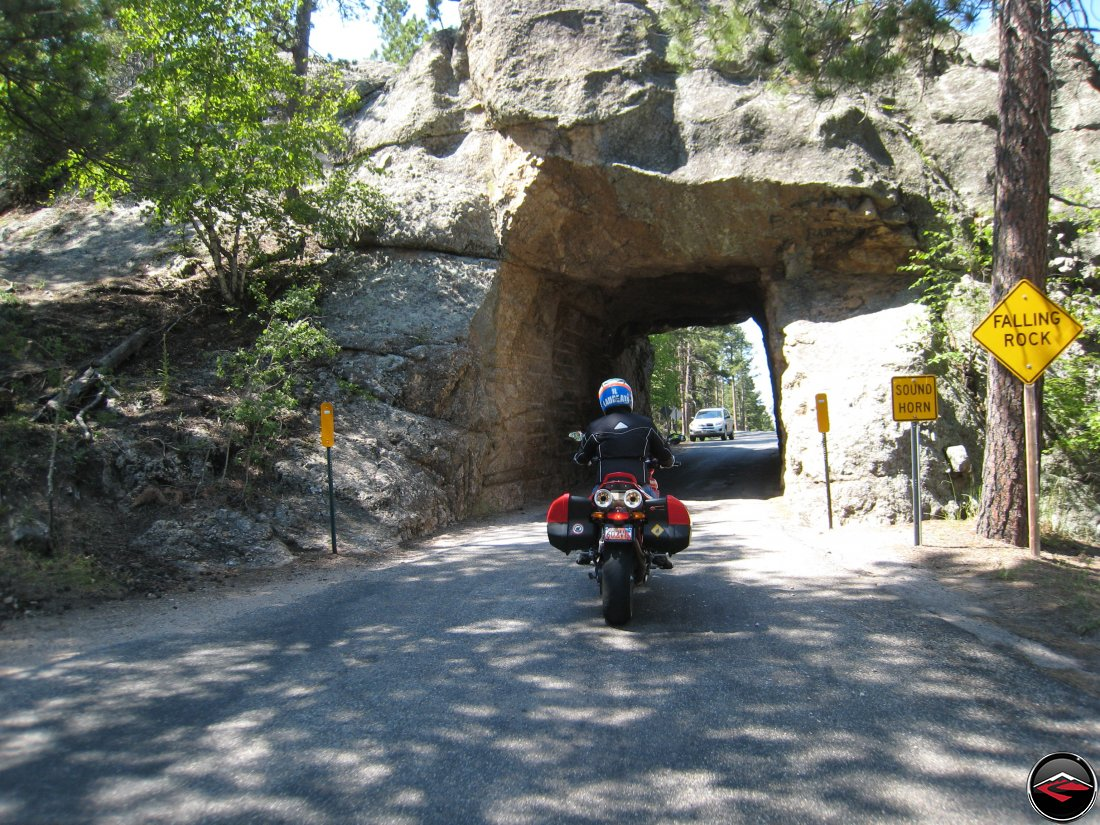 Riding a Ducati Multistrada motorcycle through one of the tunnels on the Norbeck Scenic Byway in South Dakota near Mount Rushmore