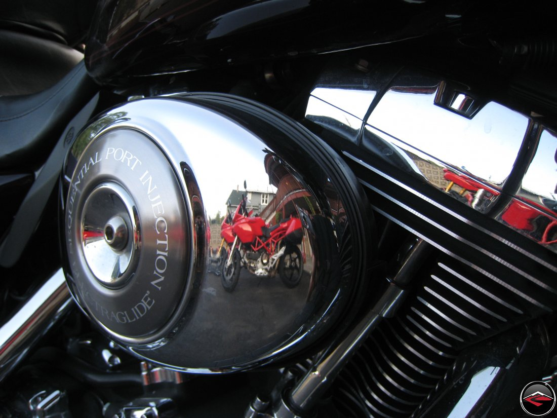 ducati motorcycles being reflected in the chrome of a harley-davidson air cleaner cover