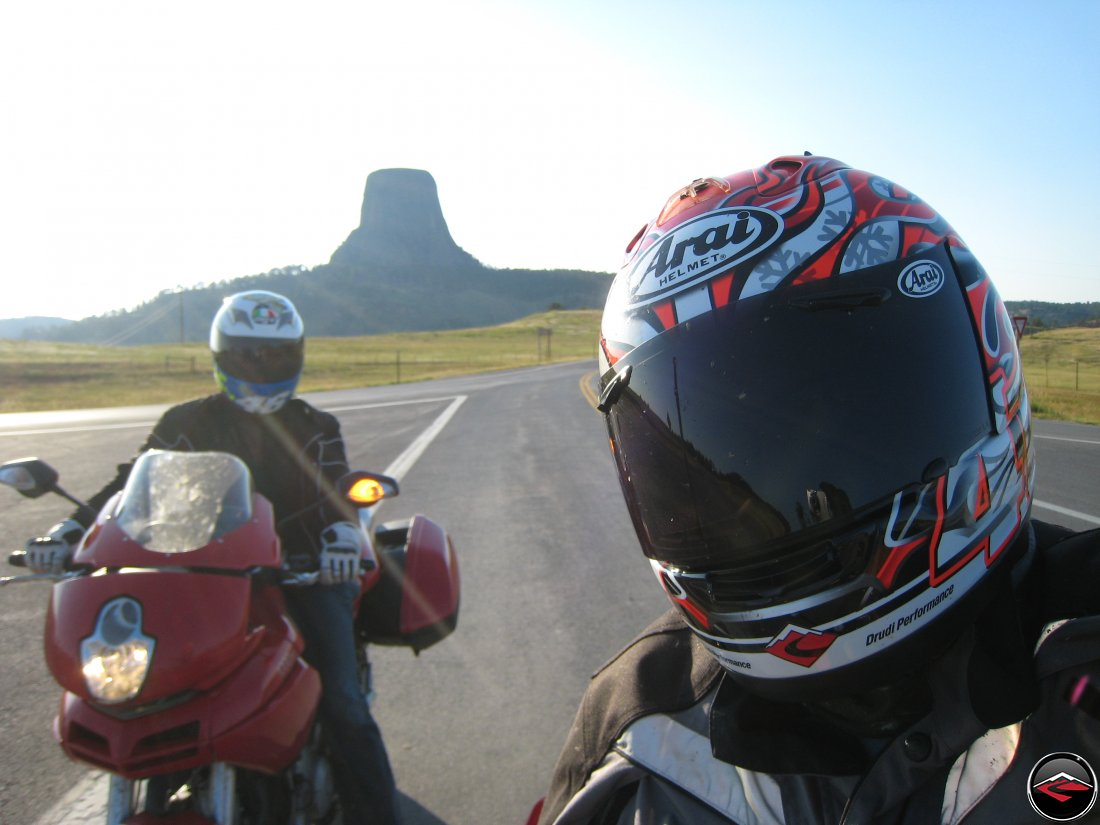 Two motorcyclists selfie with Devils Tower at Sunset behind them