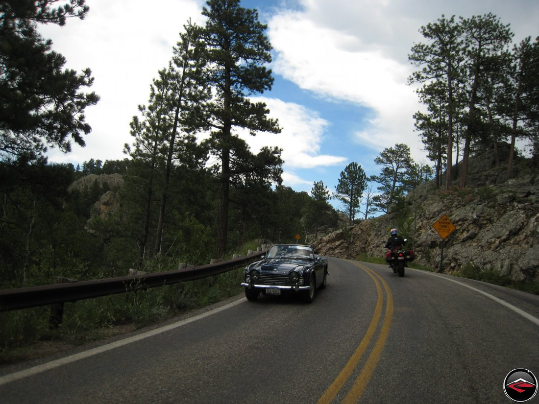 Ducati Multistrada Motorcycle passing a vintage Triumph TR3 Sports Car while riding over the Pigtail Bridges on the Norbeck Scenic Byway in South Dakota
