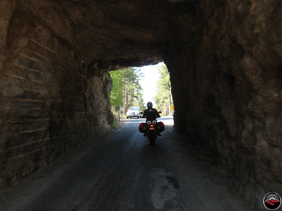 Riding a Ducati Multistrada motorcycle inside one of the tunnels on the Norbeck Scenic Byway in South Dakota near Mount Rushmore