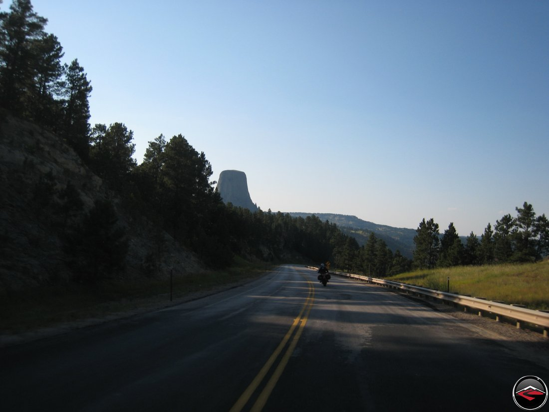 Motorcyclist on a Ducati Mulitstrada riding past Devils Tower in Wyoming