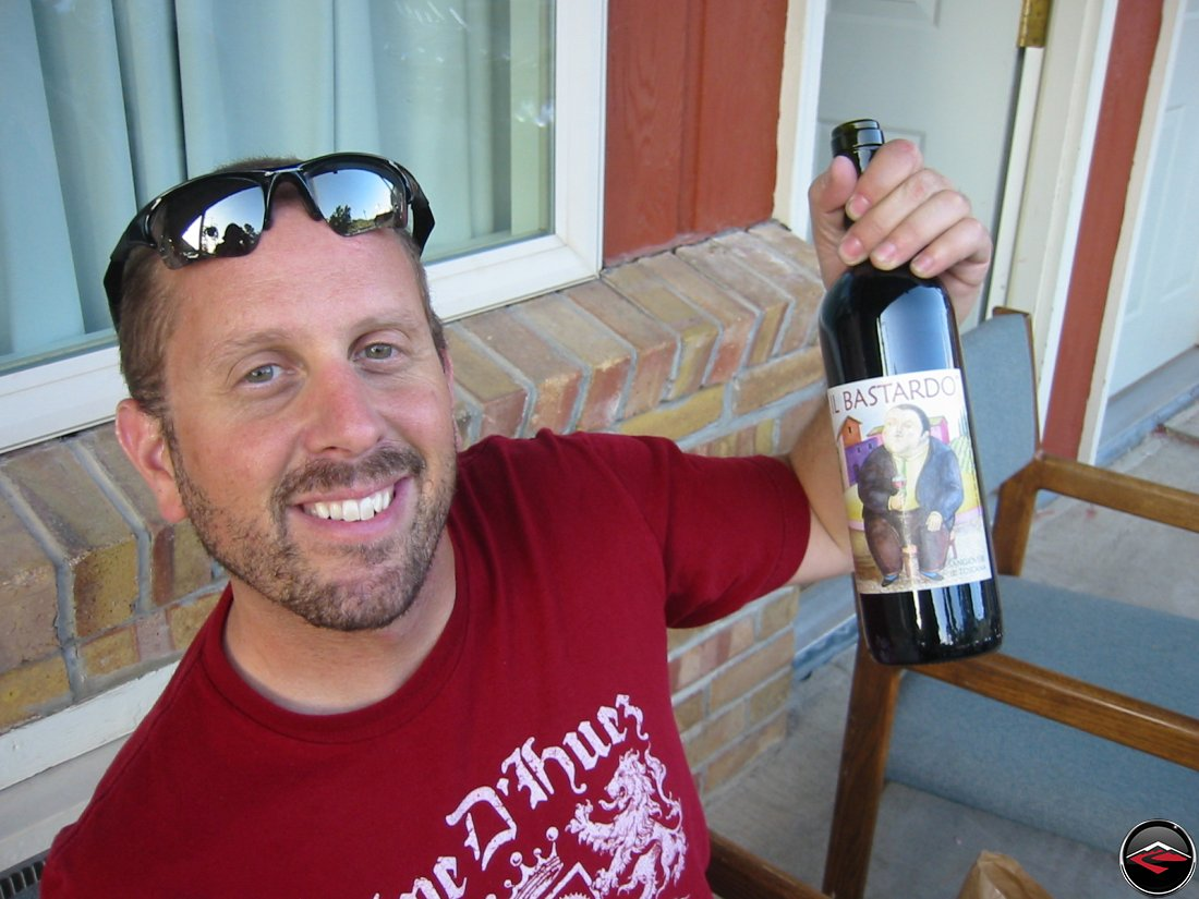 man holding up a bottle of Il Bastardo wine
