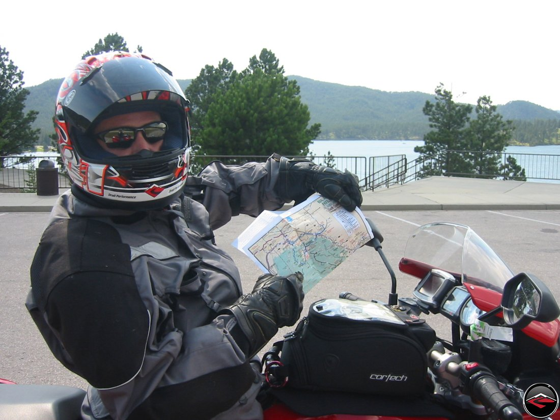 Motorcyclist wearing a full face helmet holding up a road map