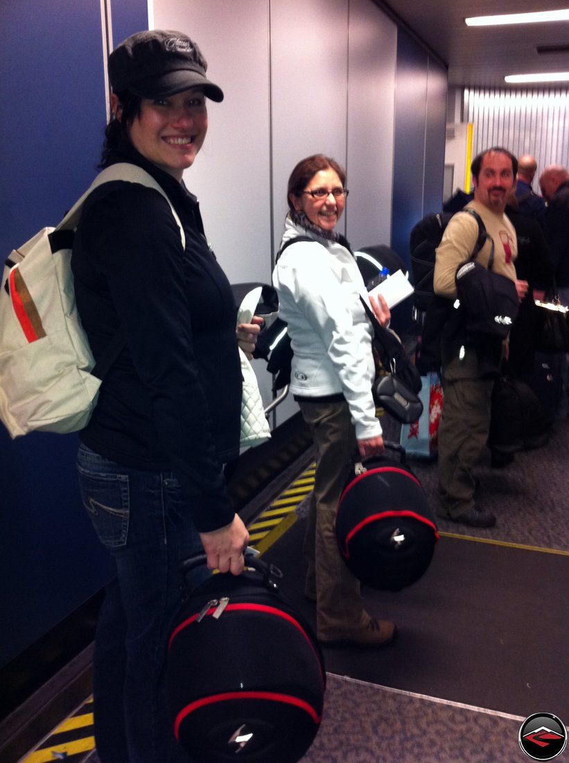 smiling and carrying helmets while boarding our first flight