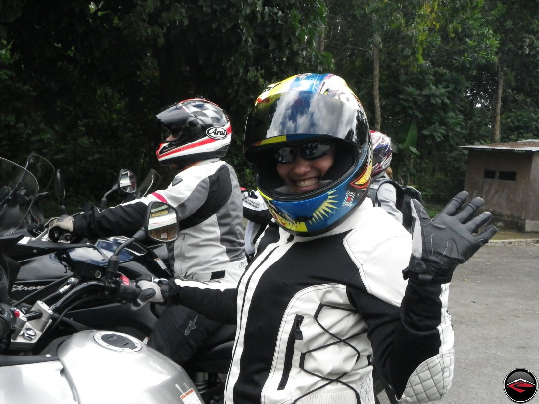 Kris, while riding her Suzuki V-Strom 650, Waves at the camera
