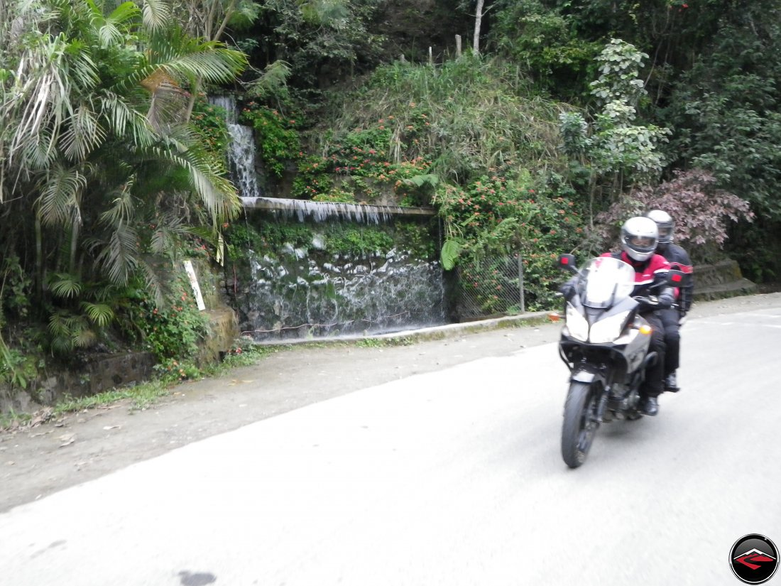 Riding a Suzuki V-Strom 650 motorcycle through a corner in the Dominican Republic