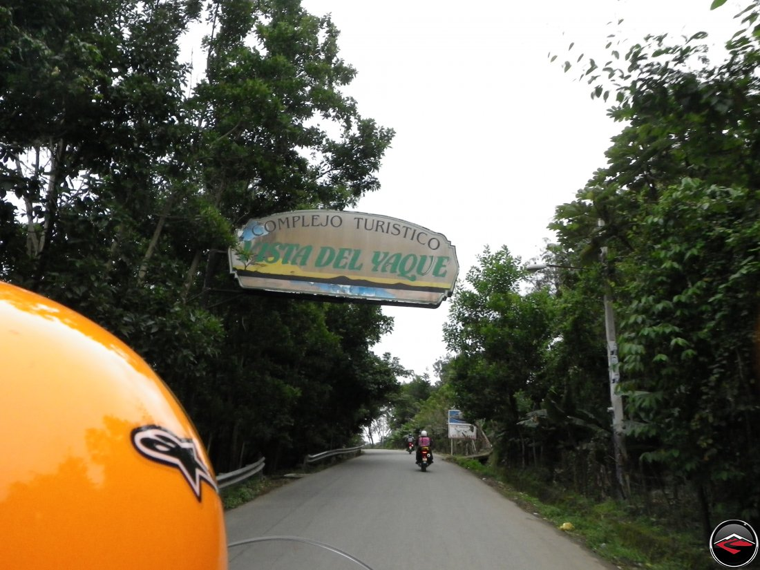 Riding motorcycles in the Dominican Republic with a sign over the top of the road that reads Complejo Turistico Vista Del Yaque