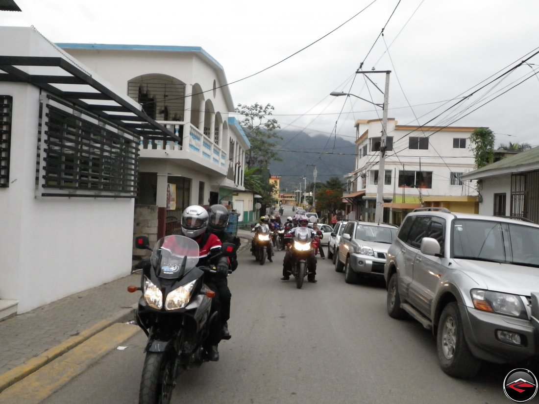 Riding motorcycles down narrow, conjested streeds of a caribbean town