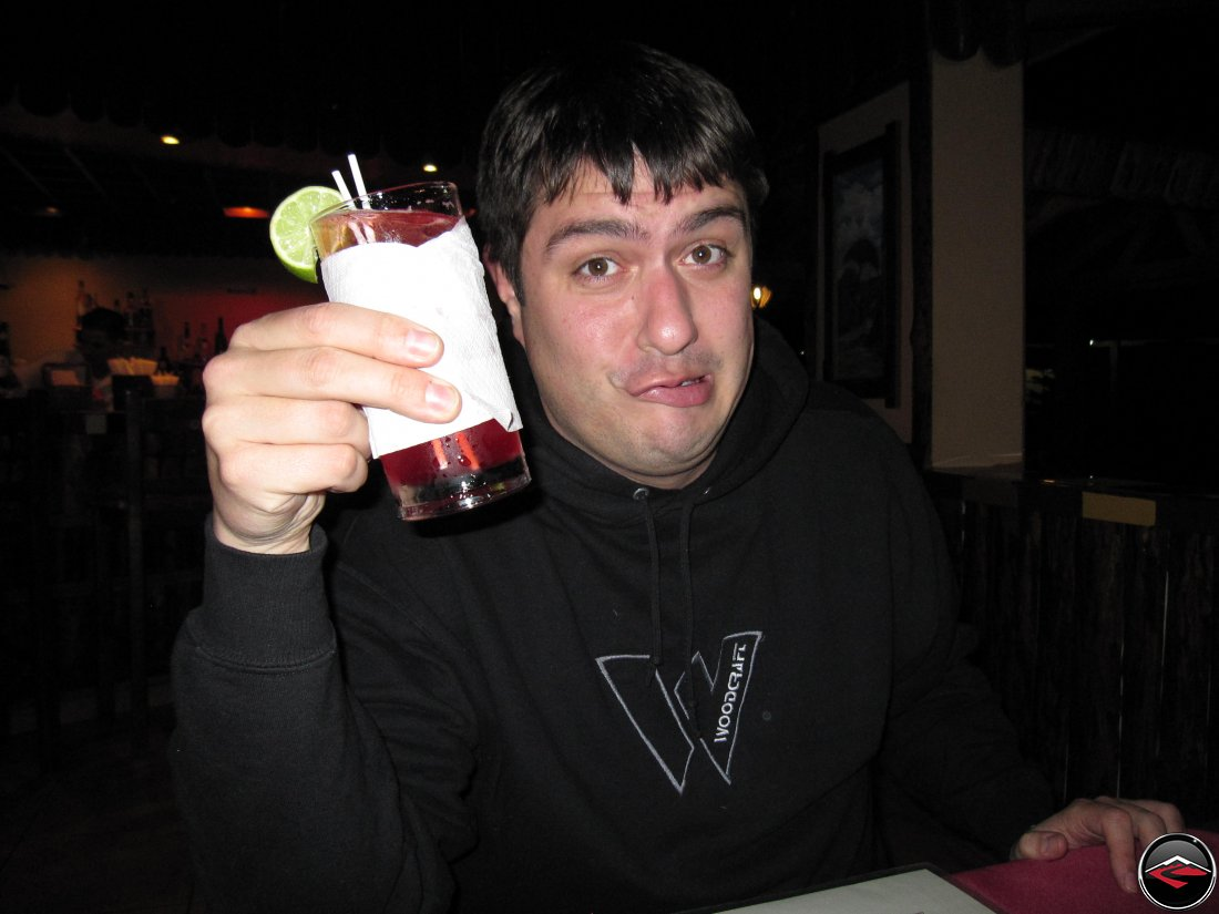 Man holding an alcoholic drink with a funny look on his face
