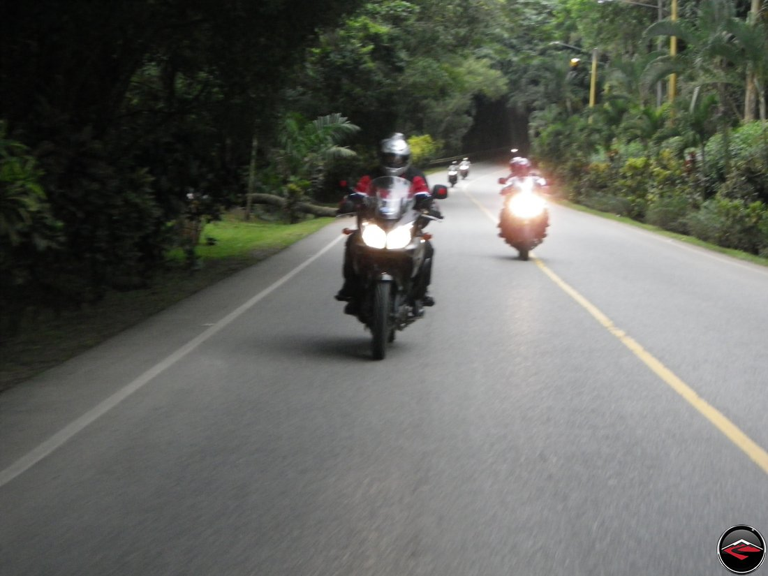 Riding Suzuki V-Strom 650 Motorcycles on highway 28 past dense caribbean island vegetation near La Vega Dominica Republic