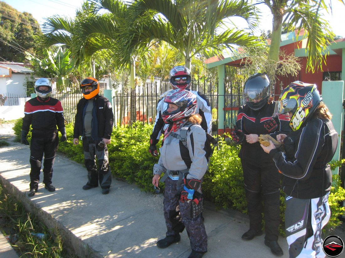 Motorcyclists standing on the sidewalk while wearing full gear in Moca Dominican Republic
