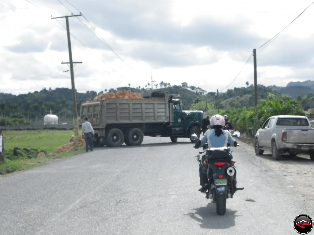 Motorcycles having to stop for a dump truck blocking the road near Sabaneta de Yasica Dominican Republic
