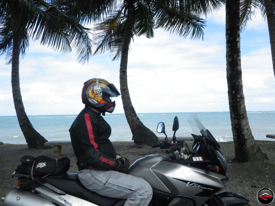 Ryan, wearing a Suomy helmet, sitting on his Suzuki V-Strom 650 Motorcycle