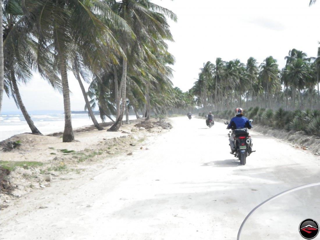 Riding motorcycles along the northern coastline of the Dominican Repblic with white sandy beaches and palm tree's blowing in the wind