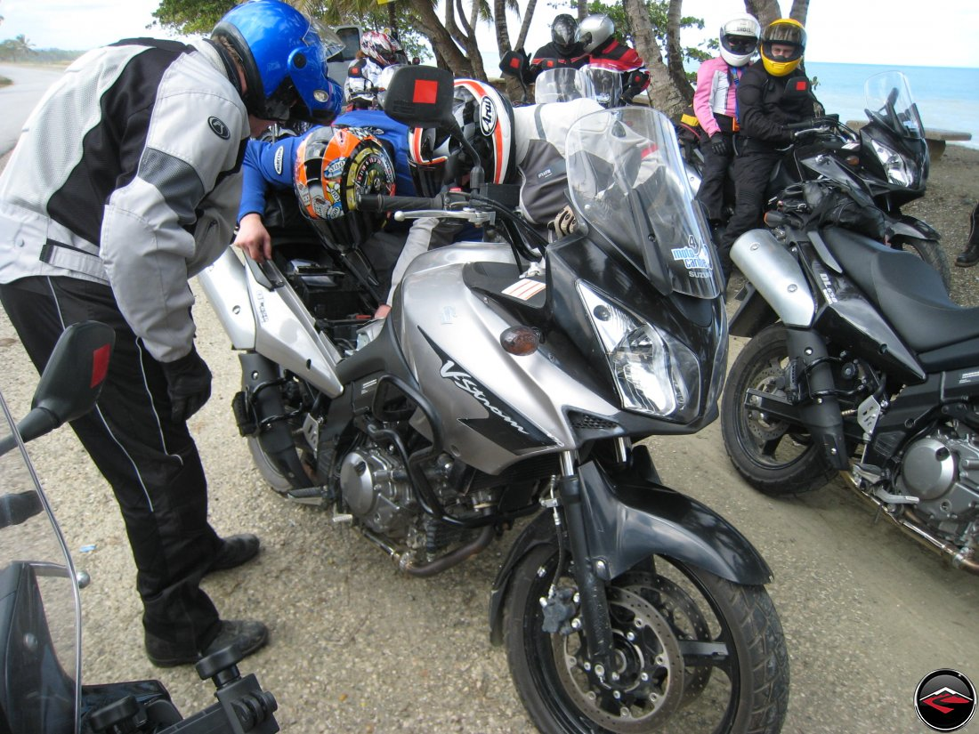 Three guys work on a loose battery connection on a Suzuki V-Strom 650 Motorcycle