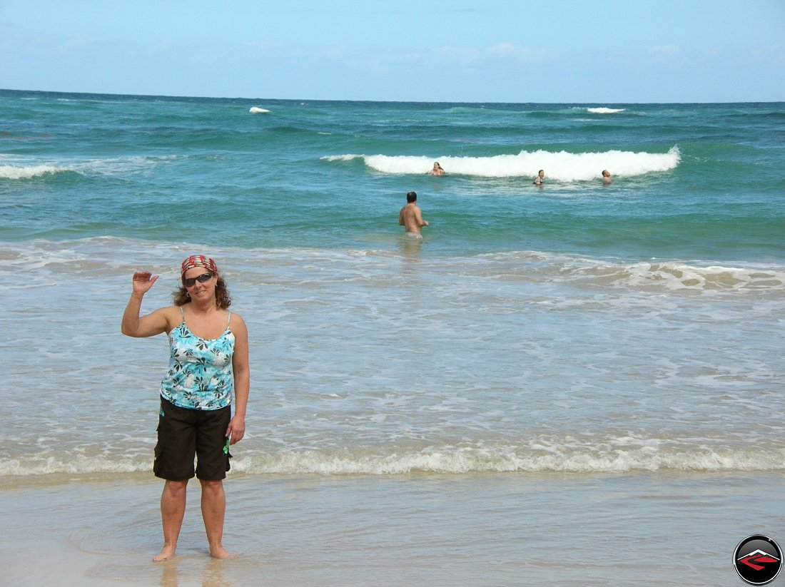 Woman standing on the beach while people play in the caribbean waters