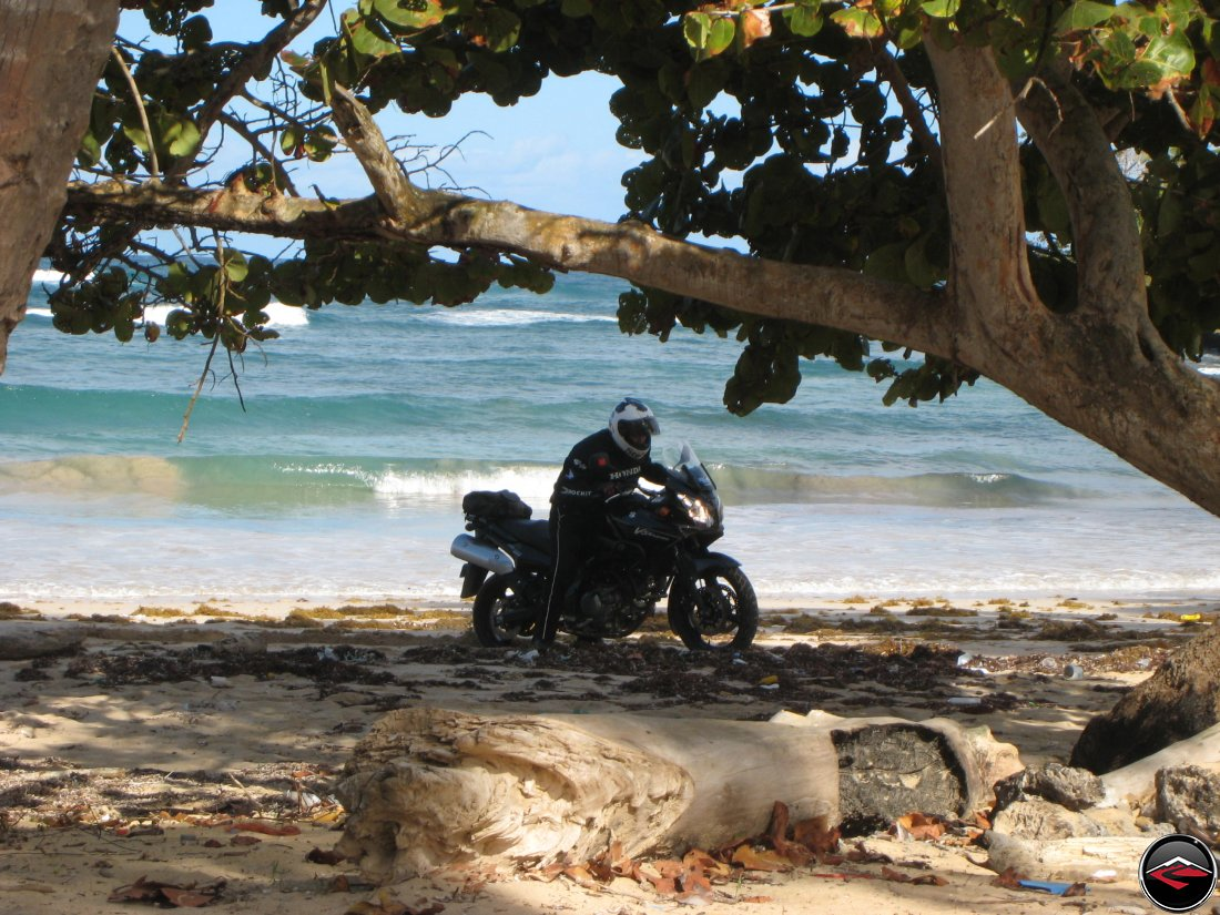 Man gets motorcycle stuck in the sand on the beach in the caribbean