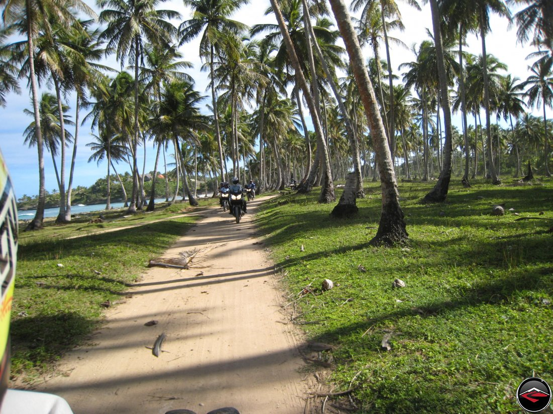Epic motorcycle riding along a perfect sandy road following the caribbean coastline of the Dominican Republic with palm trees blowing in the wind