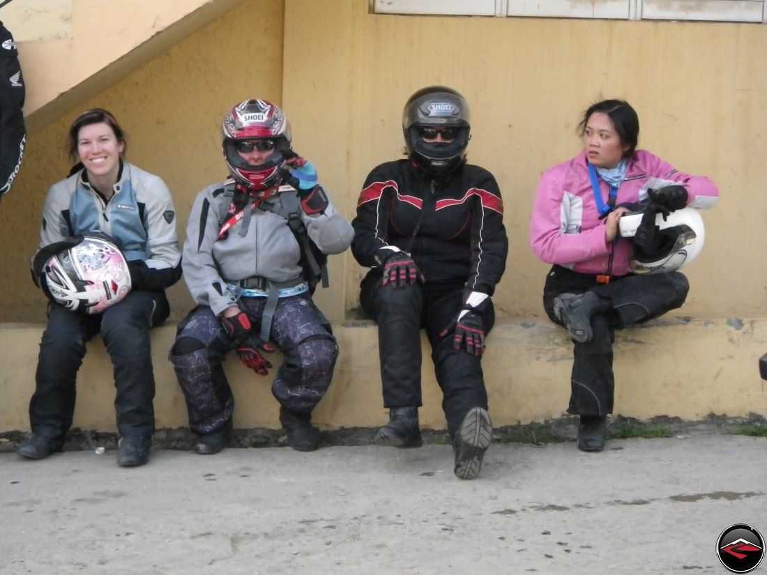 four motorcycle girls sitting on a wall