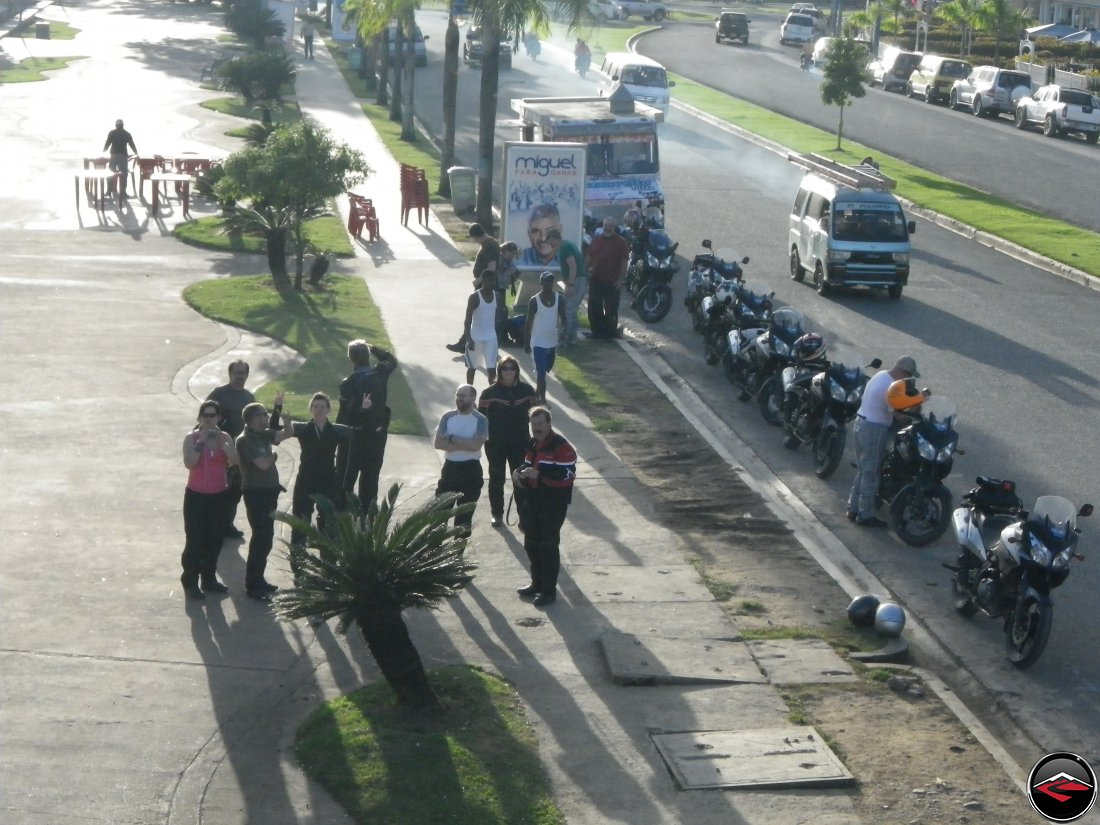 motorcycles parked along the side of the road while riders interact with locals