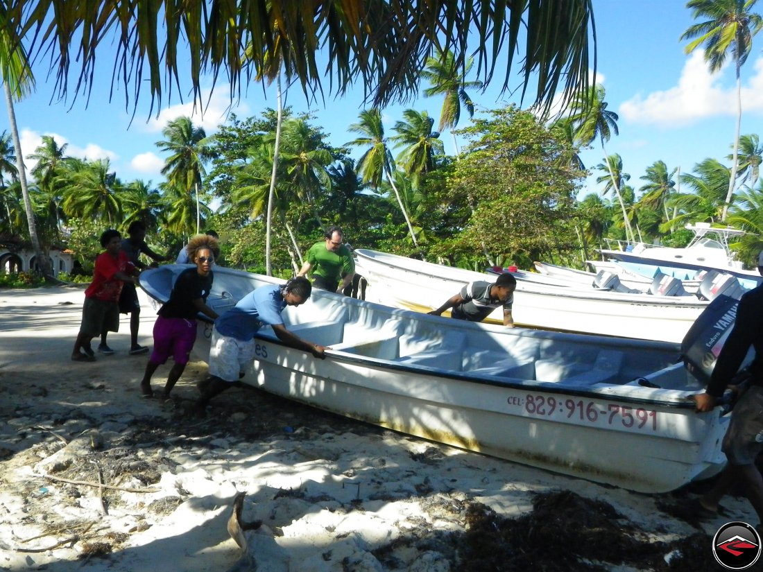 Eric helps Dominican Republic men push a boat off the beah and into the water